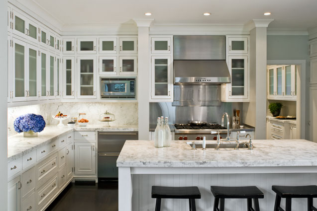 Custom white millwork cabinets with stone and beadboard island and stainless steel appliances